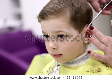 Portrait of serious kid at the barbershop - stock photo