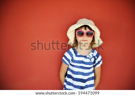 Portrait of serious little girl in white hat and sunglasses against a wall - stock photo