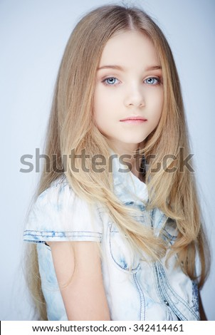 Portrait of serious little girl with blue eyes. - stock photo