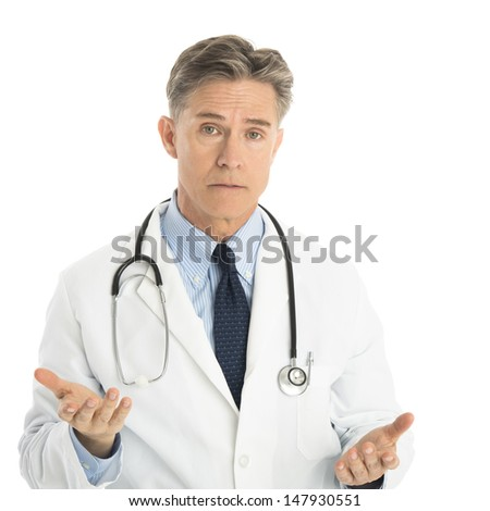Portrait of serious male doctor gesturing while standing against white background