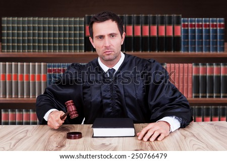 Portrait Of Serious Male Judge Striking Gavel In Courtroom - stock photo