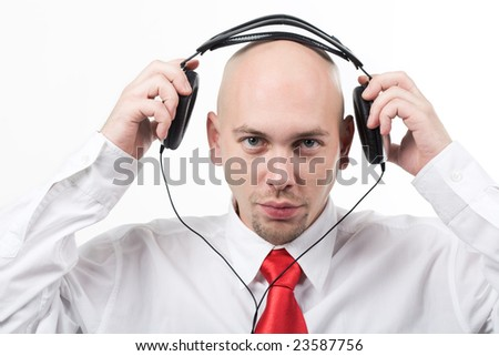 Portrait of serious male putting headphones on his head and looking at camera - stock photo