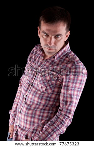 Portrait of serious man over dark background - stock photo