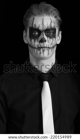 Portrait of serious man with Halloween skull makeup. Halloween or horror theme - stock photo