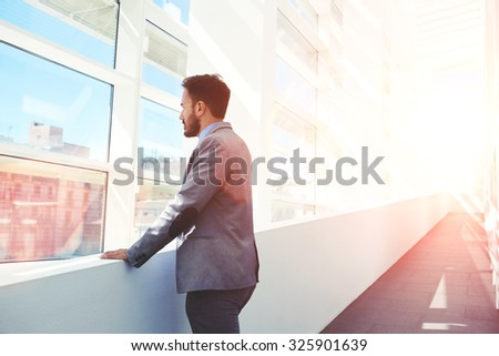 Portrait of serious men boss dressed in luxury elegant clothes watching in window while standing in modern space, thoughtful young successful male entrepreneur in suit resting after business meeting  - stock photo