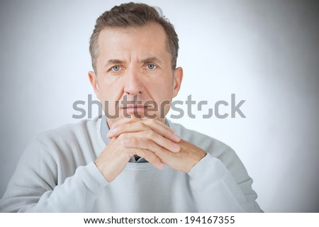 Portrait of serious middle aged businessman on gray background - stock photo
