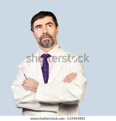 Portrait of serious middle-aged dentist, looking at copyspace and thinking, wearing lab coat, dentist mirror in his hand on a pale background.