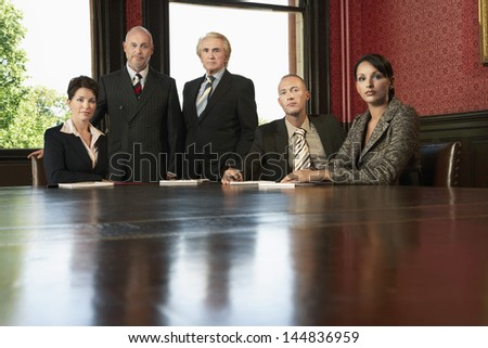 Portrait of serious multiethnic business team at conference table - stock photo