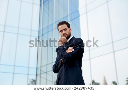 Portrait of serious pensive business man standing with arm crossed and hand against his mouth - stock photo