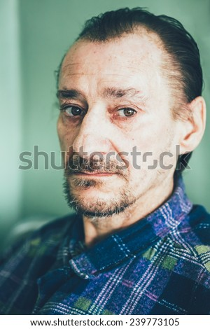 Portrait Of Serious Sad Old Adult Expressive Man With Beard Looking At Camera On Green Wall Background. Toned Photo - stock photo