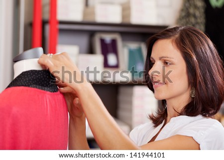 Portrait of serious saleswoman examining clothes on mannequin in clothing store - stock photo