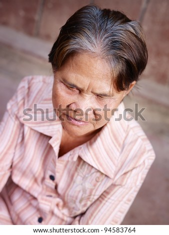Portrait of serious senior asian woman against brown wall - stock photo