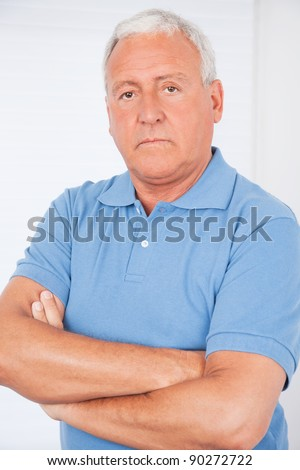 Portrait of serious senior man with arms crossed - stock photo