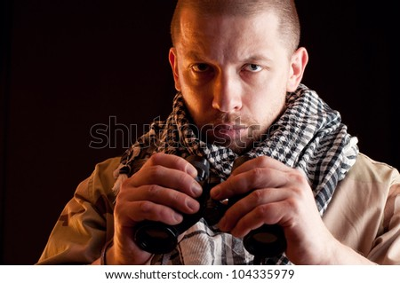Portrait of serious soldier in camouflage holding binoculars