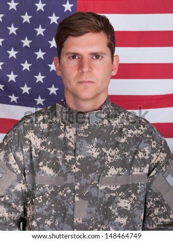 Portrait Of Serious Solider Standing In Front Of Us Flag - stock photo