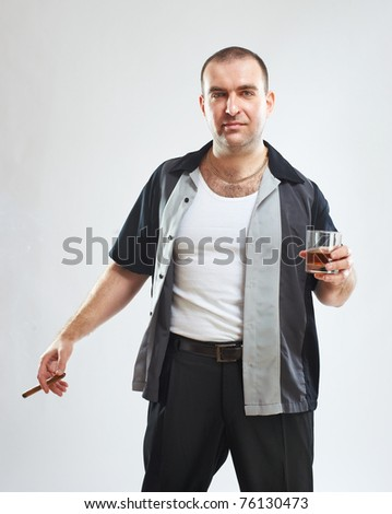 Portrait of serious tough guy with cigar and glass of alcohol, studio shot - stock photo