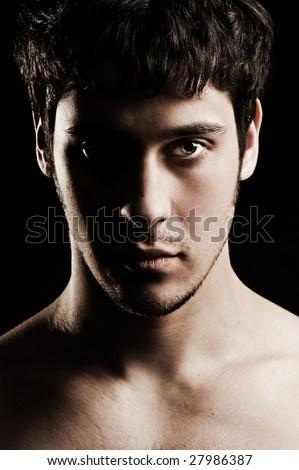 portrait of serious unshaven man against black background - stock photo
