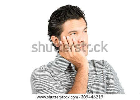 Portrait of serious, worried latino man in casual clothes, cupping chin, head in hand looking away to side at blank copy space, imaginary inserted product showing angst, perplexed thinking - stock photo