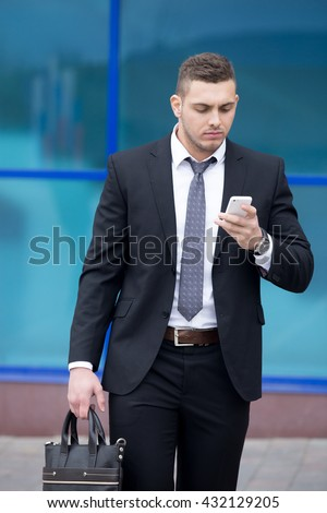 Portrait of serious young business man looking at smartphone screen while walking outdoors. Handsome caucasian man using mobile phone app, making call or messaging on the street in summer