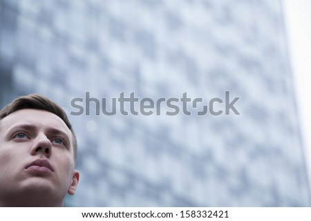 Portrait of serious young businessman looking up - stock photo
