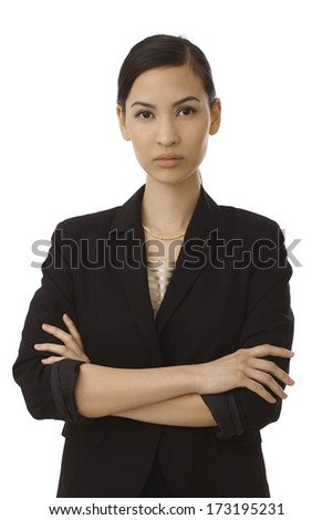 Portrait of serious young businesswoman standing arms crossed, looking at camera. - stock photo