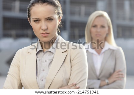 Portrait of serious young businesswoman with female colleague in background - stock photo