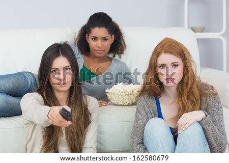 Portrait of serious young female friends with remote control and popcorn bowl on sofa at home - stock photo