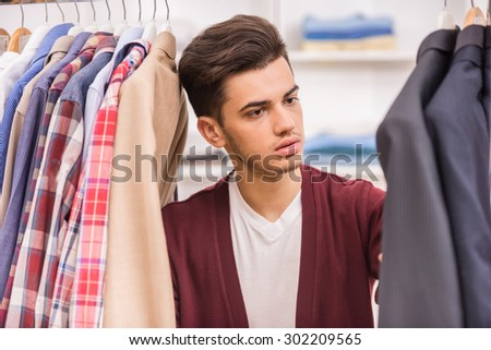 Portrait of serious young man choosing shirt in the wardrobe. - stock photo
