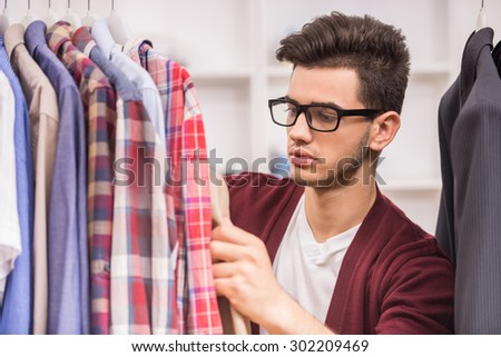 Portrait of serious young man in glasses choosing shirt in the wardrobe. - stock photo