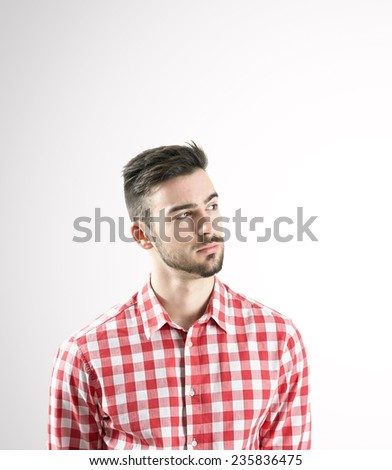 Portrait of serious young man in plaid shirt looking away over gray background. - stock photo