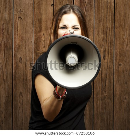 portrait of serious young woman shouting with megaphone against a wooden wall