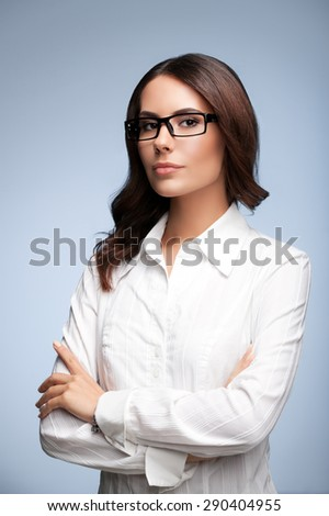 Portrait of seriously looking young businesswoman in glasses, over grey background - stock photo