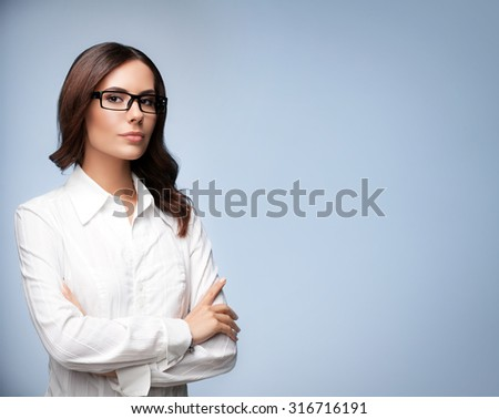 Portrait of seriously looking young businesswoman in glasses, with blank copyspace area for slogan or text message, over grey background - stock photo