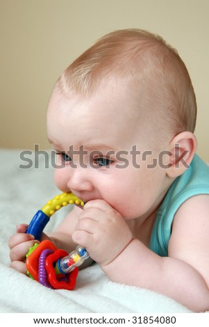 Portrait of seven months old sweet baby. A beautiful baby playing with rattle. - stock photo