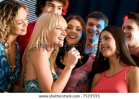 Portrait of seven young attractive friends at a karaoke party