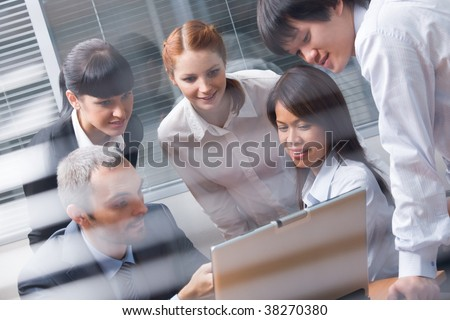 Portrait of several colleagues looking at laptop screen during meeting - stock photo