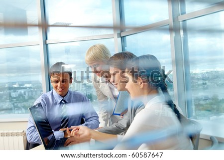 Portrait of several colleagues looking at laptop screen during meeting in office - stock photo