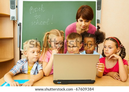 Portrait of several kids and their teacher looking at laptop screen by blackboard in classroom - stock photo