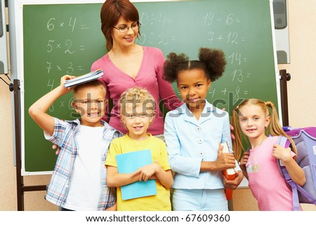 Portrait of several kids and their teacher standing by blackboard in classroom