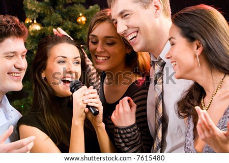Portrait of several people singing a song together at a karaoke party