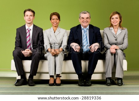 Portrait of several successful associates sitting on sofa and looking at camera - stock photo