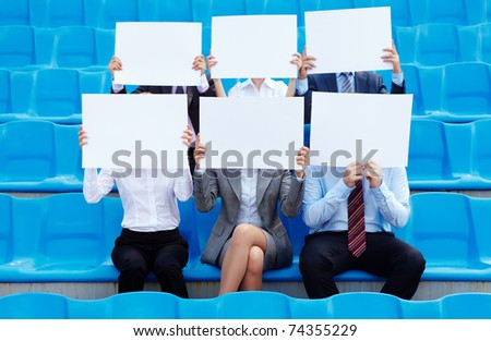 Portrait of several successful partners sitting on stadium and showing blank papers - stock photo