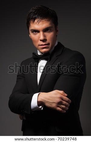 Portrait of severe man stare at camera wearing formal costume standing on dark  background - stock photo