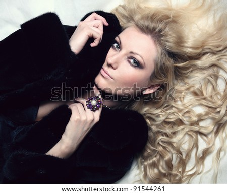 portrait of sexual blond woman dressed in fur and lingerie - stock photo