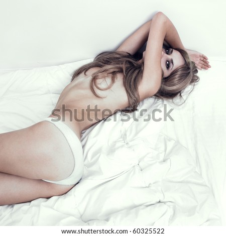 Portrait of sexual woman bent in bed - stock photo