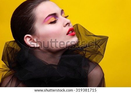 Portrait of sexual young girl in a black veil on a yellow background - stock photo