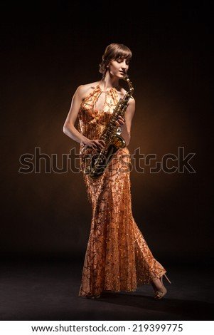Portrait of sexual young woman posing with saxophone at studio.