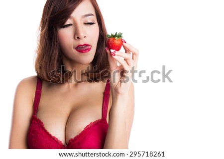 Portrait of Sexy asian woman eating strawberry, wearing red bra or lingerie on white background