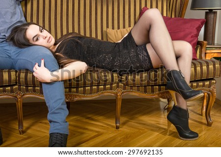 Portrait of sexy beautiful woman lying on man's leg in long heels on sofa. Female model in seductive dress posing on retro couch. Attractive person in vintage interior.Lovely naughty girl indoor. - stock photo
