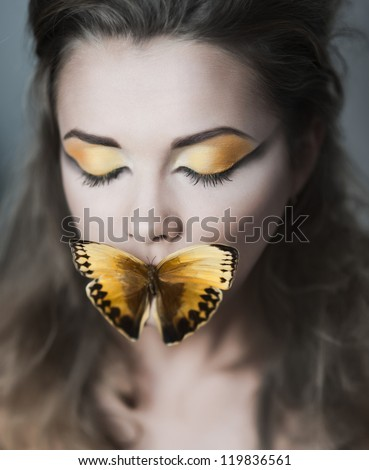 portrait of sexy beautyful young woman with a butterfly on her lips and close eyes - stock photo